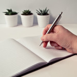 Canva - Person Holding Silver Retractable Pen in White Ruled Book